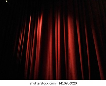 Closed red stage curtains with spotlight on them