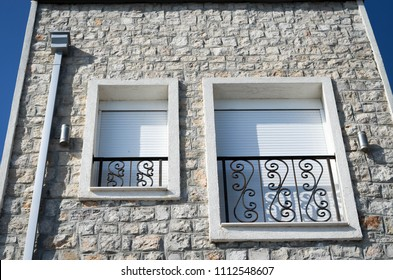 Closed rolling shutters on the window and a balcony of mediterranean stone house.  Mix of modern and vintage architecture style.