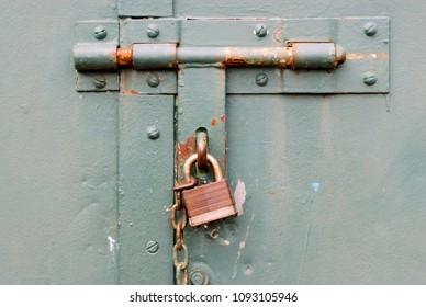 Closed rusted padlock blocking deadbolt on green steel door.