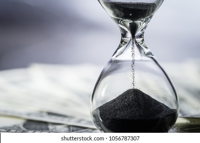 Closed up of sand falling in sandglass or hourglass on US Dollar bills as time running, long term investment or financial deadline concept.
