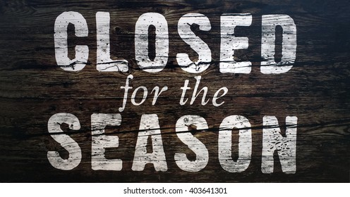 Closed for the season spray painted sign on wood.