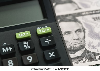 Closed up shot of TAX minus / plus buttons with text TAX RATE on calculator with background of US Dollar banknotes, United States government tax calculation.