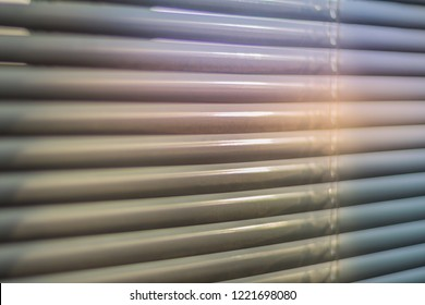 Closed shutters macro shot. Jalousie background. Sunlight through horizontal blinds.