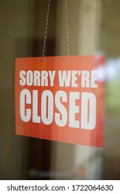 Closed sign board hanging on the glass door of cafe or small store