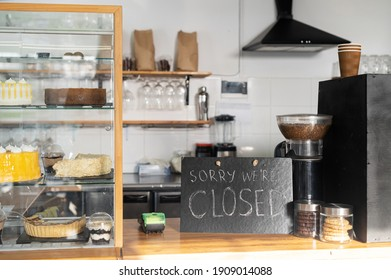 Closed sign board on the bar counter in an empty coffee shop. Cafe, bar closed due outbreak lockdown. Small business crisis concept