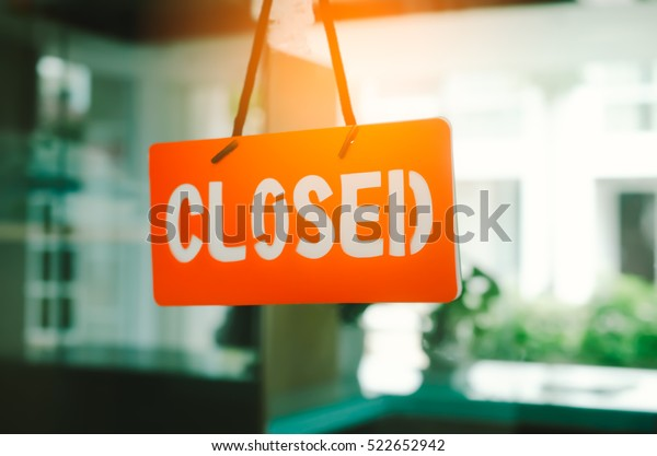Closed sign hang on mirror door front of office room. Business and service concept. Vintage tone filter color style.