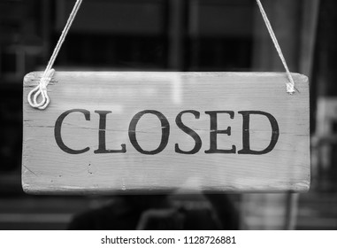 Closed sign in a shop showroom with reflections in black and white