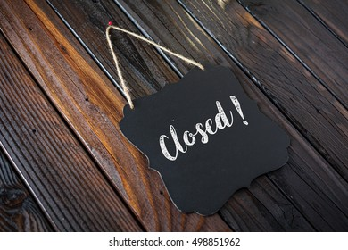 Closed Sign Written In Chalk On Chalkboard On Rustic Vintage Wood Background. Selective Focus.