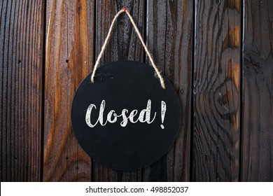 Closed Sign Written In Chalk On Chalkboard On Rustic Vintage Wood Background. Top View Selective Focus.