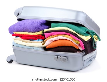 Closed silver suitcase with clothing isolated on white
