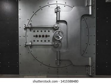 Closed steel bank vault door, close-up. Bank vault. Safe storage of valuables