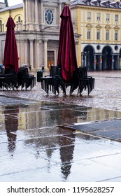closed sunshades and piled up chairs under the rain in a square in Turin, Italy, reflecing in the wet pavement