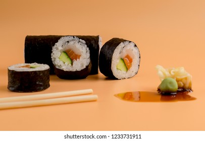 closed up sushi roll with chop sticks and wasabi, ginger