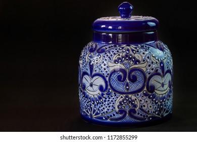 A closed Talavera vase with an elegant black background