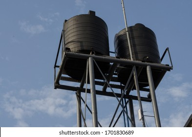 Closed up of two overhead water tanks with a communication Antenna attached taken against blue skyline in Port Harcourt, Nigeria, 2020.