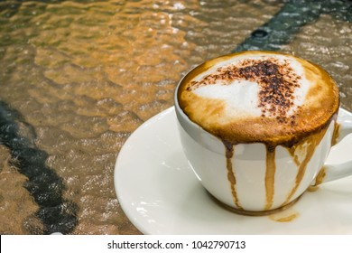 closed up, soft focus and blurred of a white cup of hot latte coffee, mess up, with  green leaf background texture, overflow on cup, on glass table