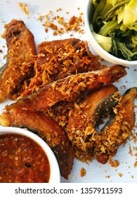 closed up view of fried fish with garlic on white dish