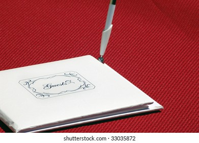"""Closed white guestbook that says """"Guests"""" on the front, with a pen standing up on it's side. It is on a red table cloth."""
