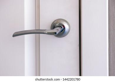 Closed white interroom door with handle. Close-up.