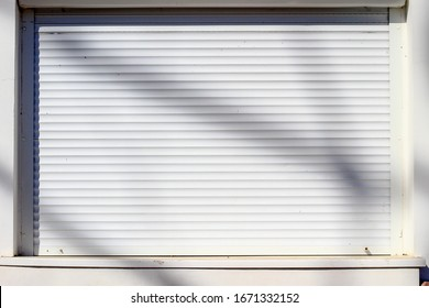 Closed white store shutters due to a coronavirus pandemic