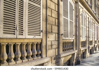 Closed white window shutters on top of vase-shaped balusters are warmed by the late day sunlight on an old building in Paris France.