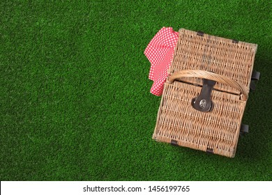 Closed wicker picnic basket on green grass, top view. Space for text