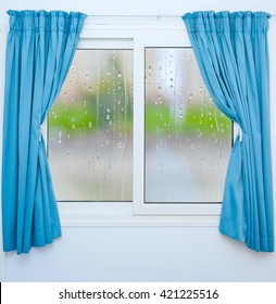 Closed window with curtains in rainy autumn weather