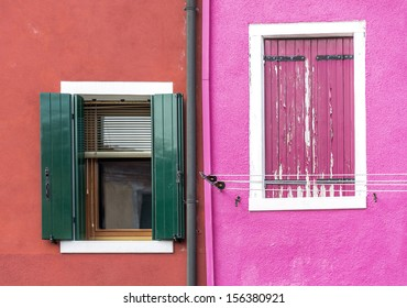 Closed window on the ancient magenta wall of the house and open window - Burano, Venice, Italy