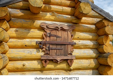 Closed window shutters with lock in yellow wooden house