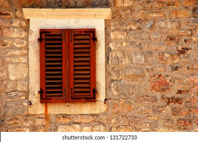 Closed window with shutters in old rough stone wall of ancient italian house. image with copy space