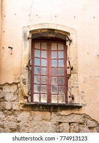A closed window of a stone building  in the village of Beaucaire, France.