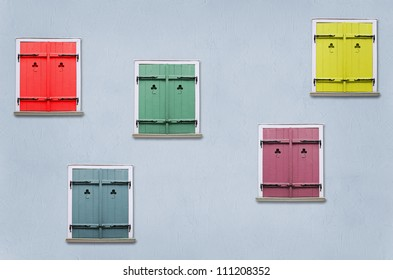 closed windows with colorful shutters in the blue house wall