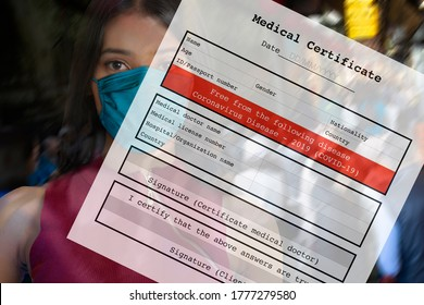 Closed up woman face with blank personal medical certificate form free from colonavirus disease or COVID-19.