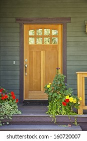 Closed wooden door of a home with green siding and flowerpots in daytime.