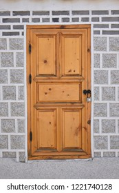Closed wooden door made from pine wood with steel handle and steel padlock on asia flat vintage grey granite wall.