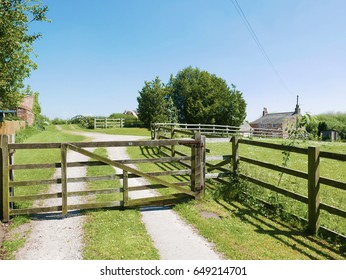 Closed wooden farm gate blocks path leading to farmhouse