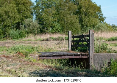 Closed wooden fence entrance to a meadow of a farm