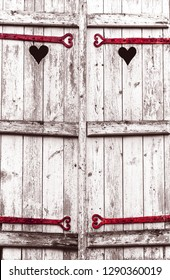 Closed wooden shutters with heart shape carving and hinges. Retro style toned aged photo. Spooky Valentine concept. Grungy romance background.