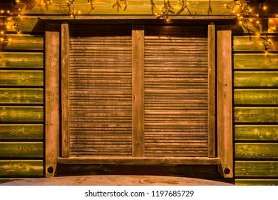 Closed wooden shutters. Light garland. Iinterior