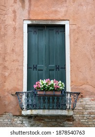 Closed wooden shutters in an old wall with small bacony and pretty window box