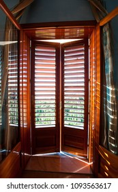 Closed wooden shutters on balcony window. Look from inside to outside. Colored inspiring vertical image. Part of italian architecture.