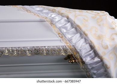 closed wooden white coffin covered with white ritual blanket isolated close-up.