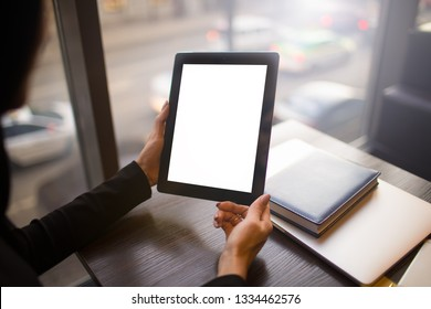 Closely business woman holding modern portable touch pad with empty mock up copy space screen background for promotional content, sitting at desktop in office. Digital gadget with blank display