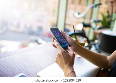 Closely businesswoman using applications on modern mobile phone while sitting at desktop in office interior. Female blogger posting article via cell telephone. Copy space for promotional content