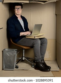 Too closely concept. Full length portrait of confused businessman is sitting in cramped carton office while holding modern laptop on his knees. He is looking at camera disappointedly