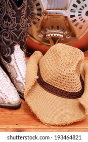 Closely cropped details of snakeskin cowboy boots with a cowboy hat and a dobro on wooden table. Only the resonator can be seen of the guitar. The hat is floppy and misshapen and has a brown band.