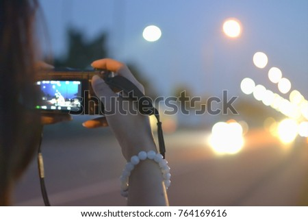 Closely image of female hand holding digital camera and taking photo beside the road at night.