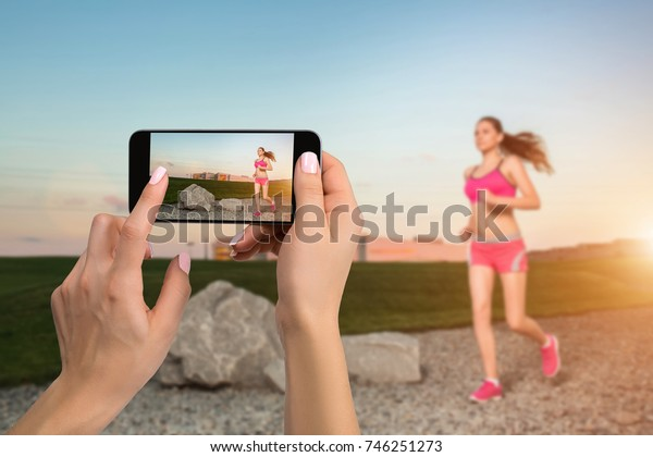 Closely image of female hands holding mobile phone with photo camera mode on the screen. Cropped image of running woman. Runner jogging in sunny nature.