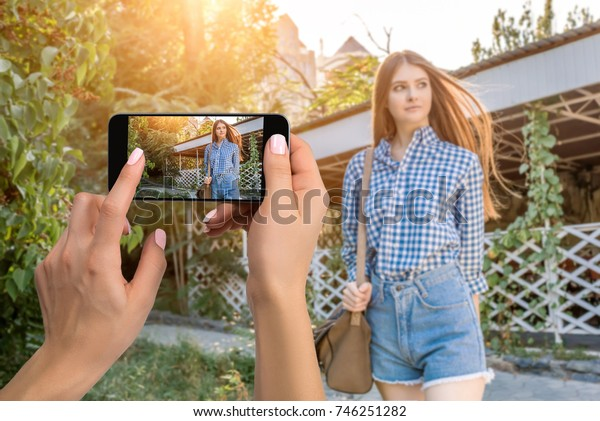 Closely image of female hands holding mobile phone with photo camera mode on the screen. Cropped image of portrait of a beautiful young woman on the streets city