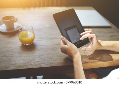 Closely image of a female searching website in network via touch pad while sitting at the wooden table in cafe, woman's hands holding digital tablet with copy space screen for your advertising content